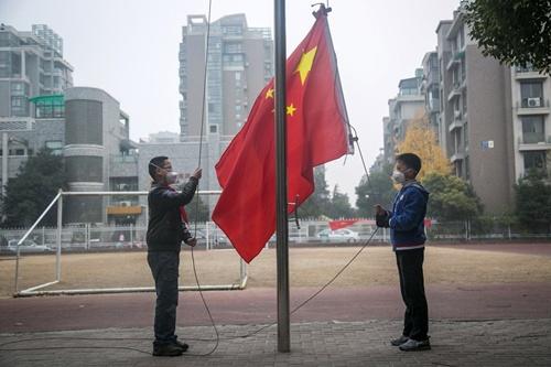 Khi cả lớp đang chào cờ trong nhà, hai học sinh đeo khẩu trang làm lễ thượng cờ ngoài trời.